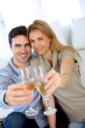 Couple holding glass of champagne towards camera photo