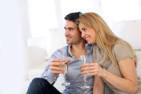 Romantic couple drinking wine at home photo
