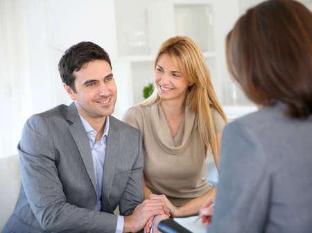 good news: Cheerful couple receiving good news from advisor Stock Photo