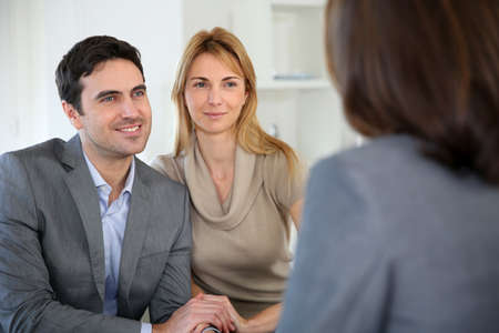 adviser: Cheerful couple receiving good news from advisor Stock Photo