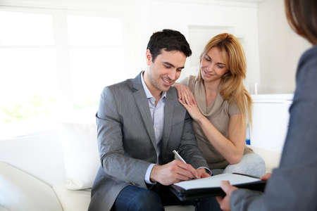 Couple signing terms of real-estate contract photo