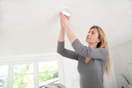 Woman setting up fire alarm inside house photo