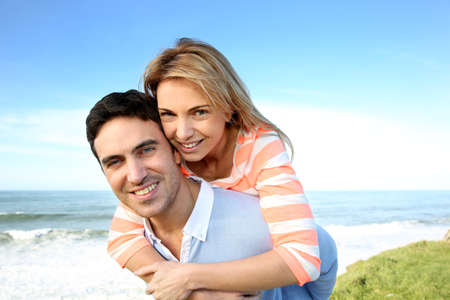 35 years old: Man giving piggyback ride to girlfriend by the sea