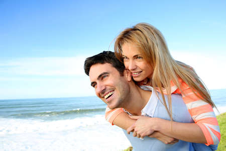 Man giving piggyback ride to girlfriend by the sea photo