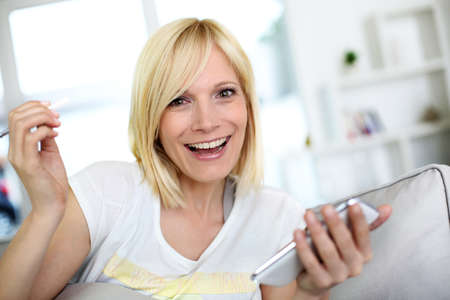 Smiling young woman at home using smartphone photo