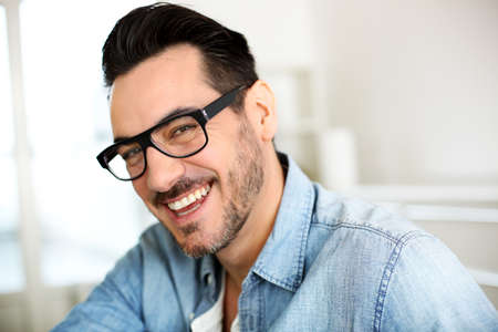 Cheerful handsome trendy guy with glasses photo