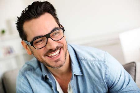 s úsměvem: Veselá trendy chlap s černými brýlemi na