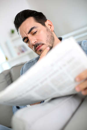 Man at home reading bad news on newspaper photo