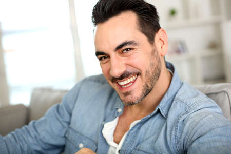 Handsome middle-aged man relaxing in sofa photo