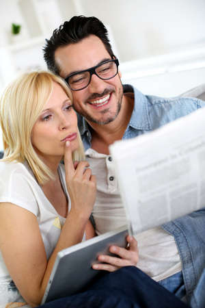 Couple at home reading news photo