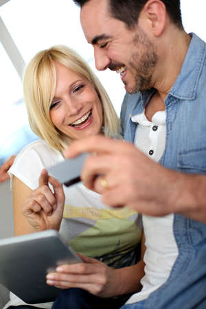 Cheerful couple at home doing online shopping photo