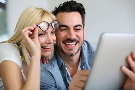 Cheerful couple websurfing on internet with tablet photo