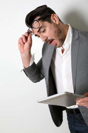 Man looking at tablet with surprised look photo