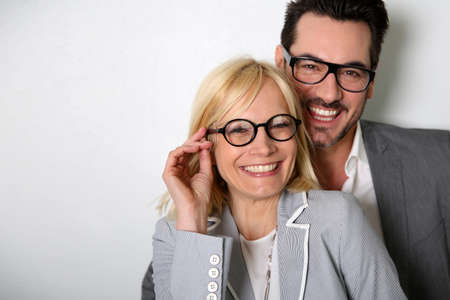 Cheerful couple with eyeglasses on white background photo
