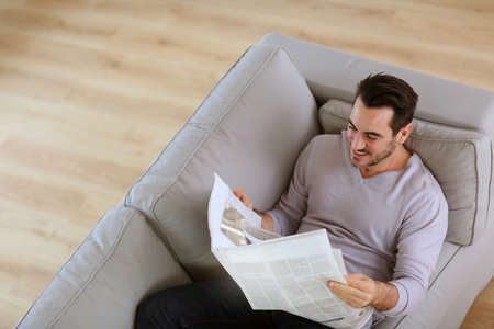 Upper view of man reading newspaper in sofa photo