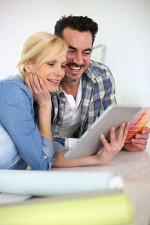 Middle-aged couple choosing wall colours for new home photo