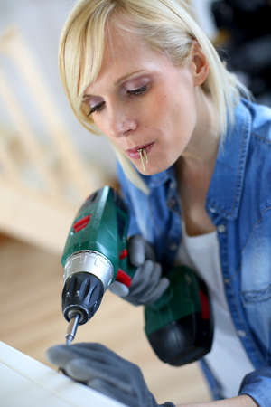 doityourself: Woman at home using electric drill
