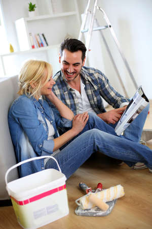 Couple sitting on the floor choosing paint colour photo