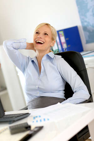 Cheerful businesswoman relaxing in office Stock Photo - 18939538