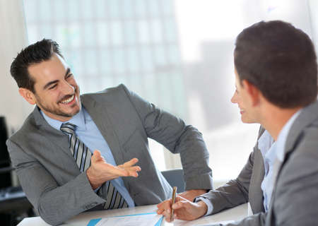 Businessman presenting contract to partners photo