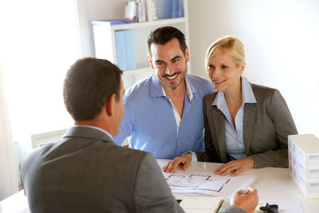 banker: Couple meeting real-estate agent to buy property Stock Photo