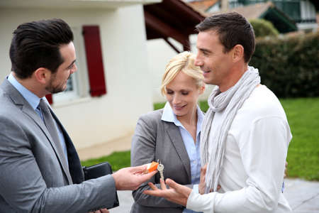 property agent: Salesman giving home keys to property owners