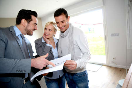 Middle-aged couple visiting house with salesman photo