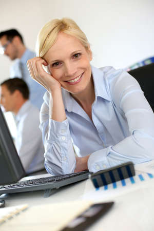 Cheerful businesswoman sitting in front of desktop Stock Photo - 18941704