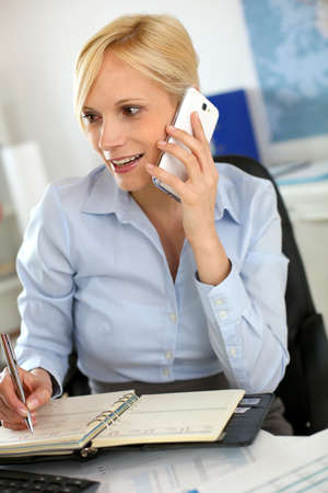 Businesswoman on the phone taking note on agenda Stock Photo - 18941756