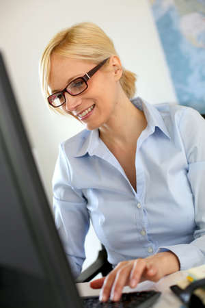 Smiling businesswoman typing on desktop keyboard Stock Photo - 18941705