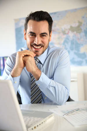 businessman with laptop: Portrait of businessman sitting in office