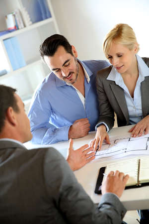 realestate: Couple meeting real-estate agent to buy property Stock Photo
