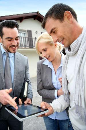 Real-estate-agent weer huis plan op digitale tablet