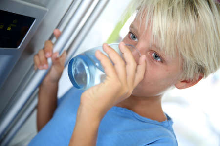 beverage fridge: Young boy drinking water from fridge Stock Photo