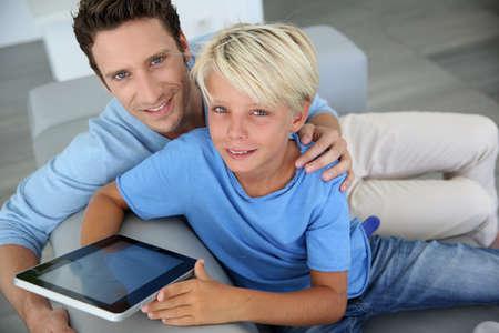 blonde yeux bleus: Père et fils à l'aide tablette numérique à la maison Banque d'images