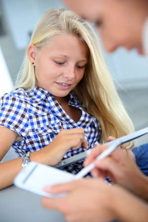 blonde teenager: Girls using tablet and smartphone together Stock Photo