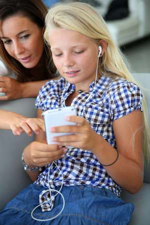 Teenager using smartphone with adult beside her photo