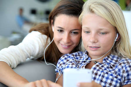 phonecall: Teenager and woman listening to music with smartphone