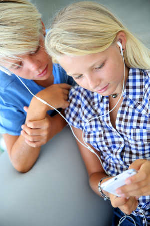 earphone: Teenagers using smartphone with earphones Stock Photo