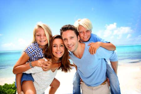 persona feliz: Los padres que dan a cuestas paseo a los ni�os en la playa