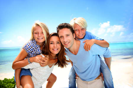 happy teenager: Parents giving piggyback ride to kids at the beach Stock Photo