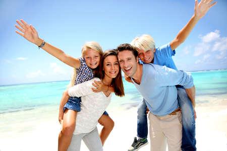 piggyback: Parents giving piggyback ride to kids at the beach Stock Photo