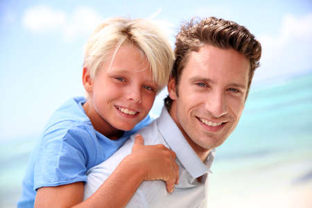 Daddy giving piggyback ride to son by the beach photo