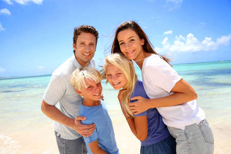 family holidays: Happy couple with kids at the beach Stock Photo
