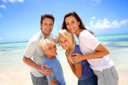 familia abrazo: Pareja feliz con los ni�os en la playa