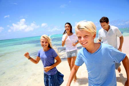 Cheerful family running on a sandy beach photo