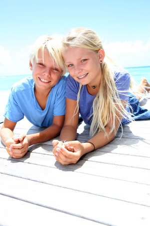 Blond teenagers laying on pool deck in summer photo