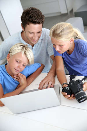 kids laptop: Man with teenagers looking at pictures on computer