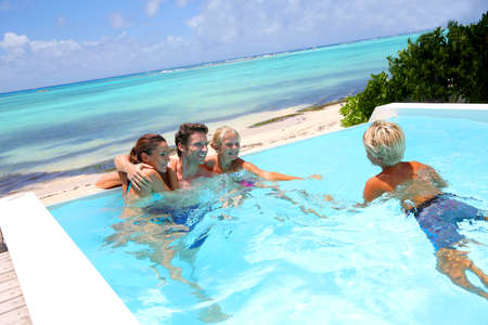 Parents and kids in swimming pool photo