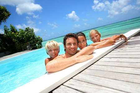 caribe: Family of four bathing in swimming pool